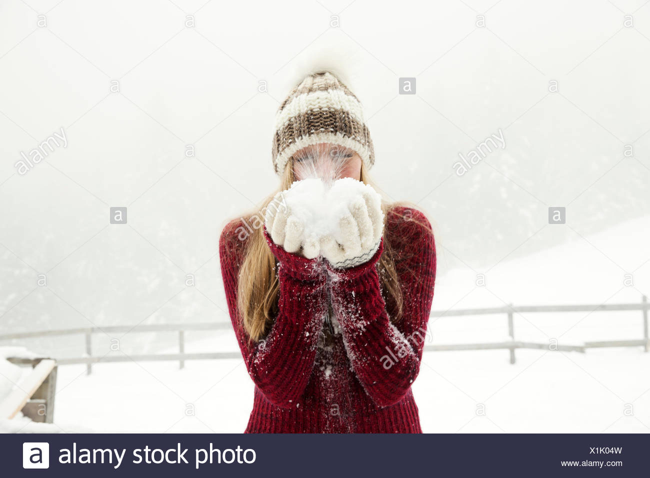 Young woman blowing handful of powder snow - Stock Image