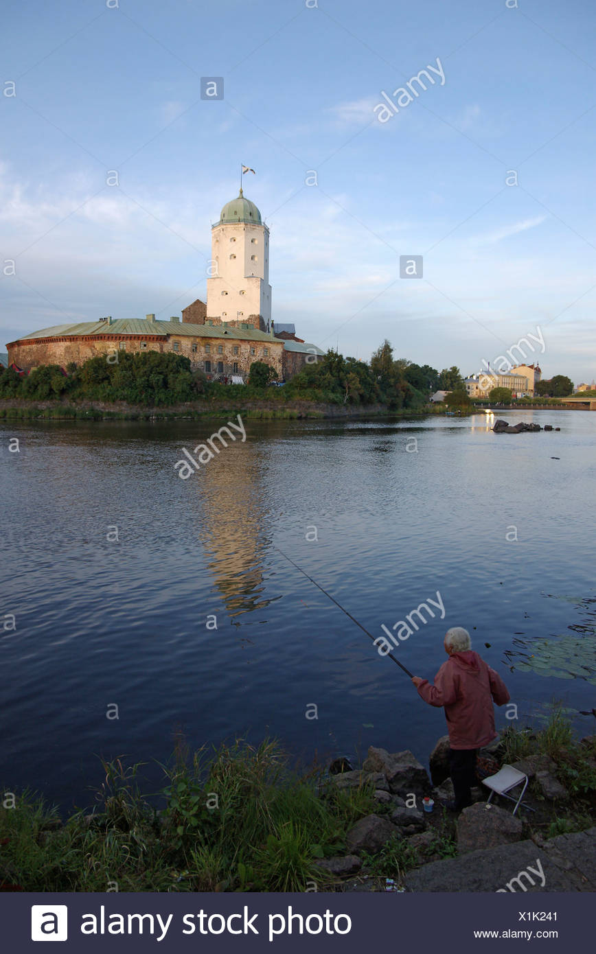 Old lady fishing in Vyborg St Olaf s tower in background Russia - Stock Image