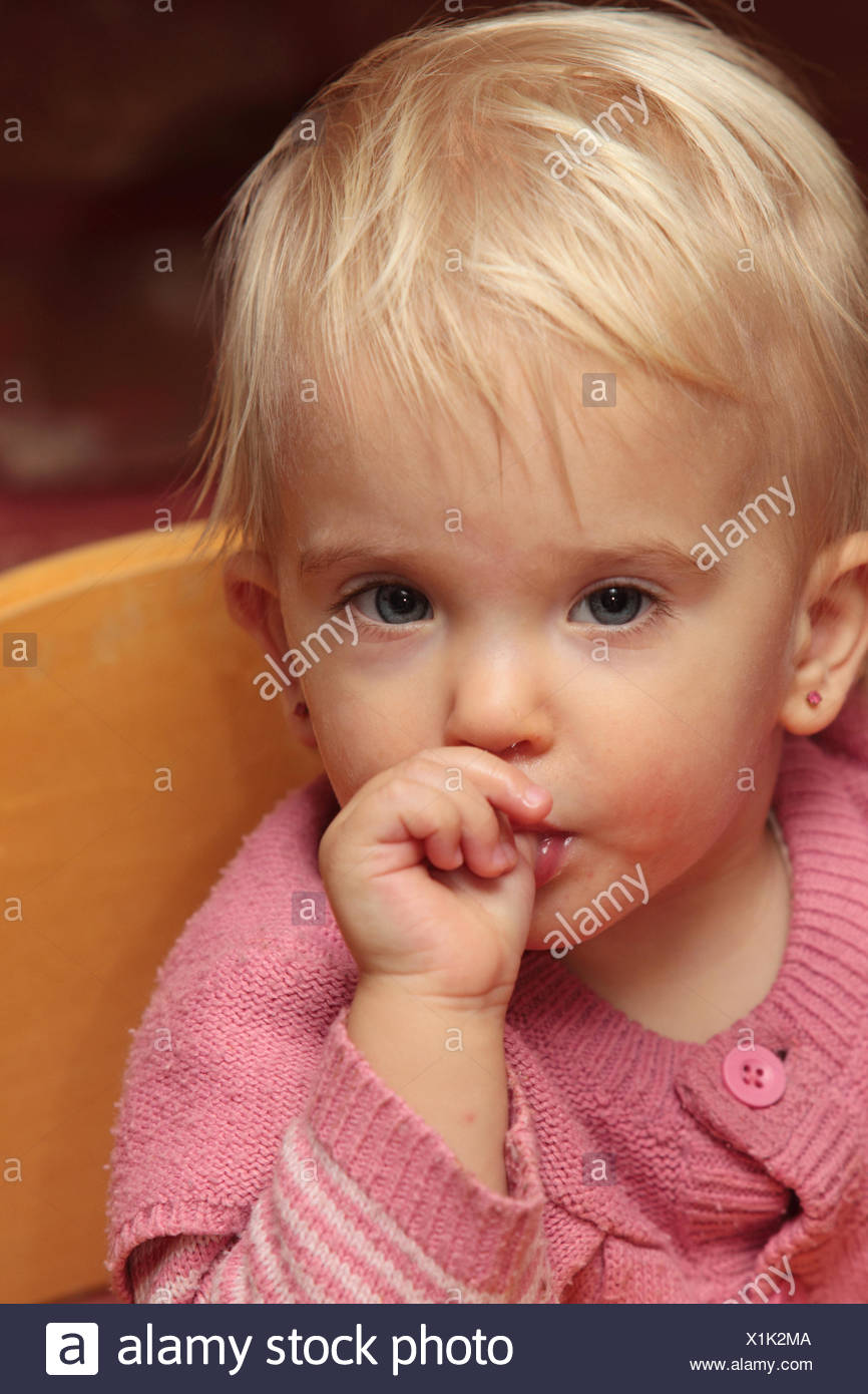 Portrait of an eighteen-months-old baby girl sucking her thumb. - Stock Image