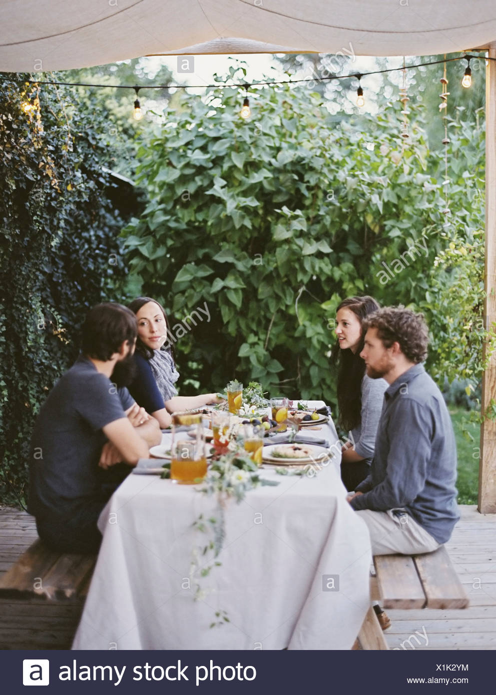 Four people seated at a table in the garden Place settings and decorations on a white tablecloth Two men and two women - Stock Image
