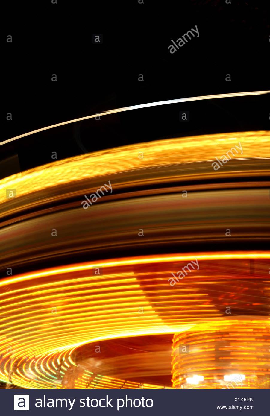 Rotating fairground ride at night - Stock Image