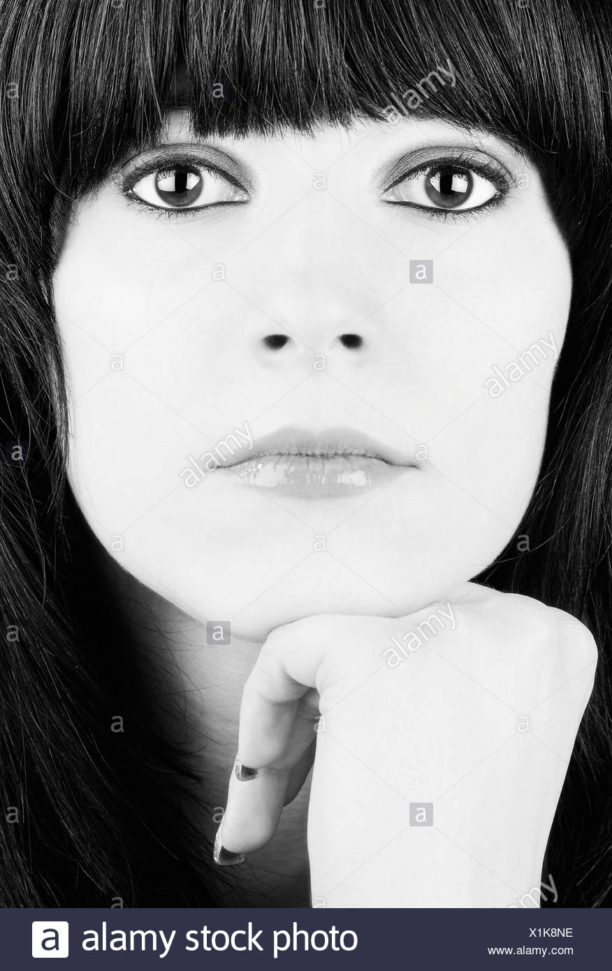 Portrait of a girl with black hair and big eyes resting her chin on her hand, black and white - Stock Image