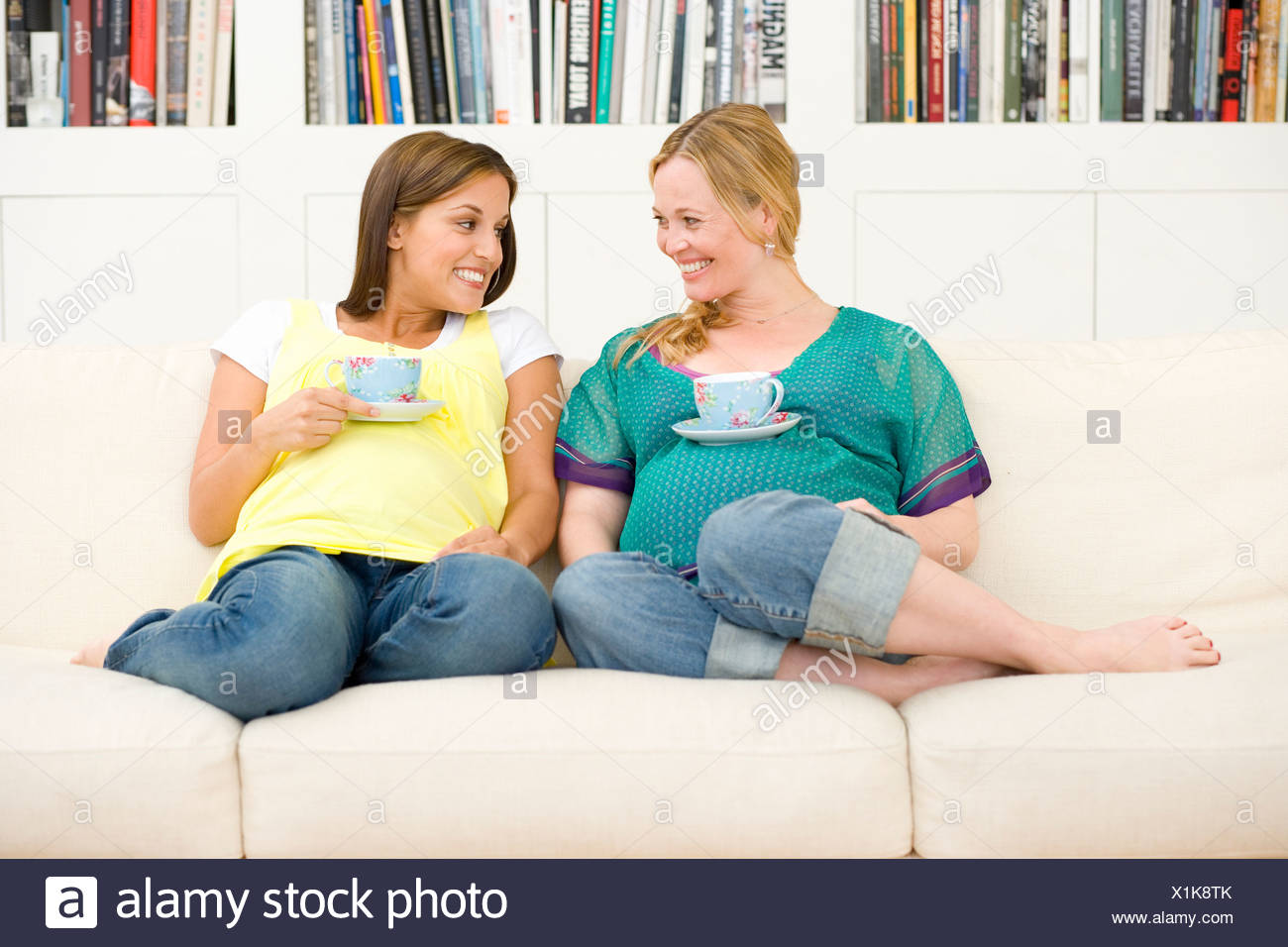 Two young pregnant women on sofa with mugs resting on stomachs, smiling at each other, low angle view - Stock Image