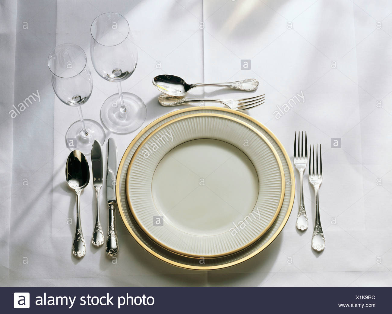 Table setting gold-rim plates cutlery fish cutlery glasses & Table setting: gold-rim plates cutlery fish cutlery glasses Stock ...