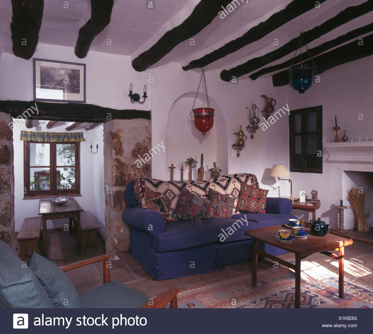 Patterned cushions and throw on blue sofa in Spanish cottage ...