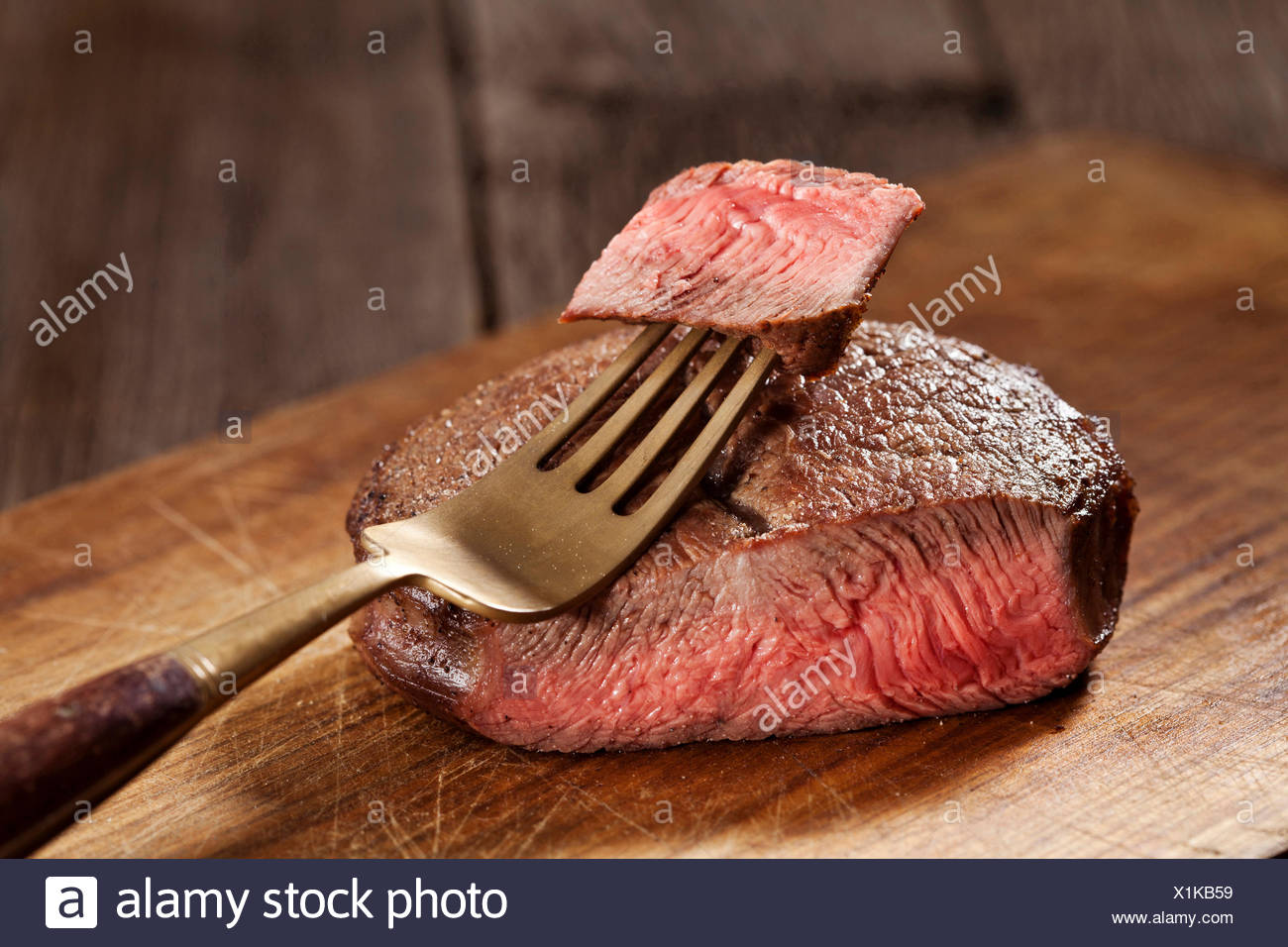 Beef steak cooked to medium rare on wooden background - Stock Image