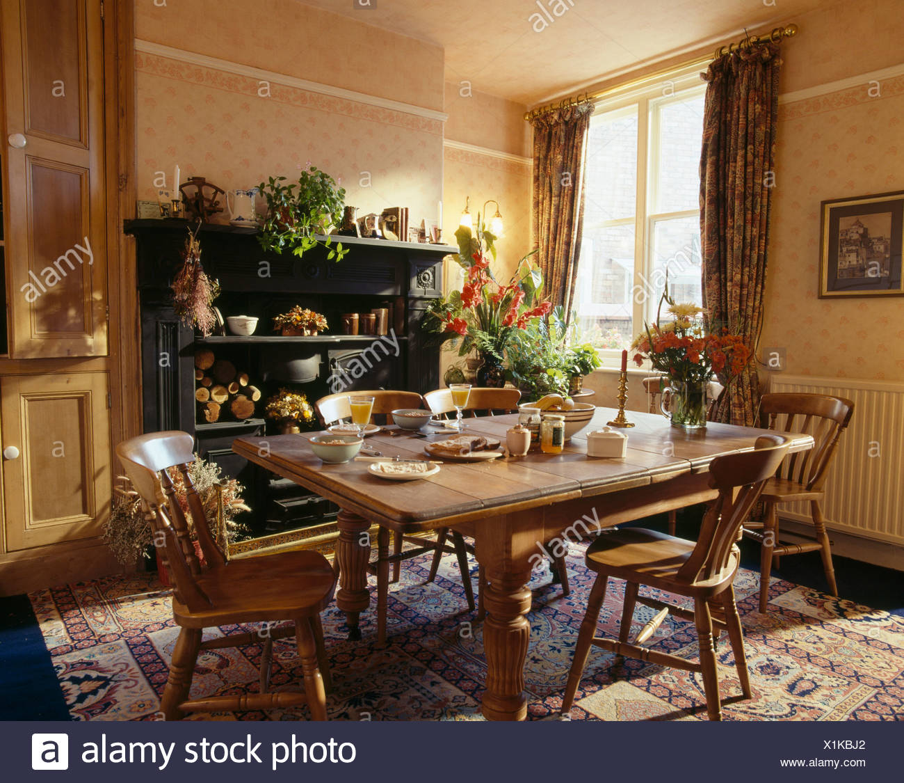 Pine chairs and table in traditional dining room with neutral patterned wallpaper