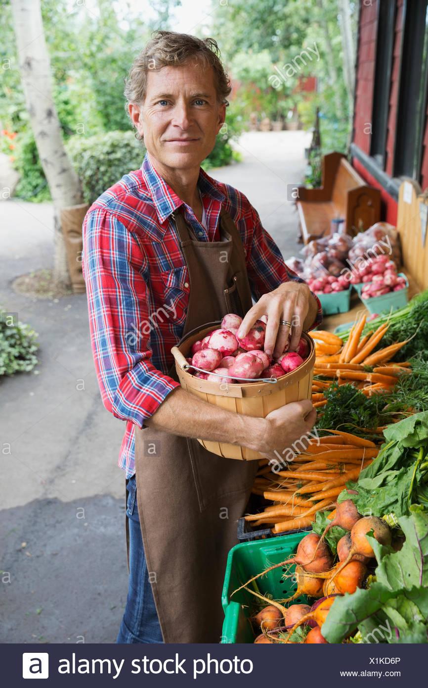 Portrait of worker stocking produce outside market - Stock Image