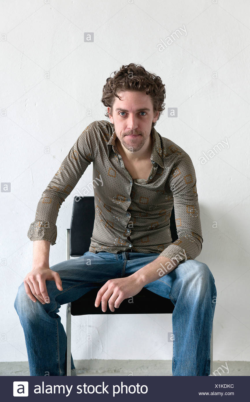 Mid adult man sitting on chair, smiling, portrait Stock Photo