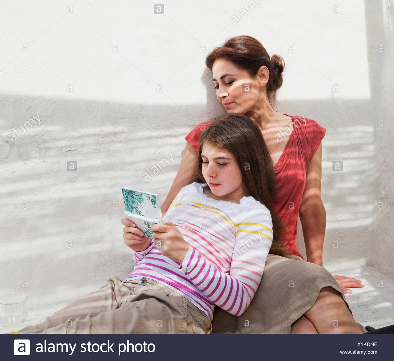 Mother and daughter with hand held device - Stock Image
