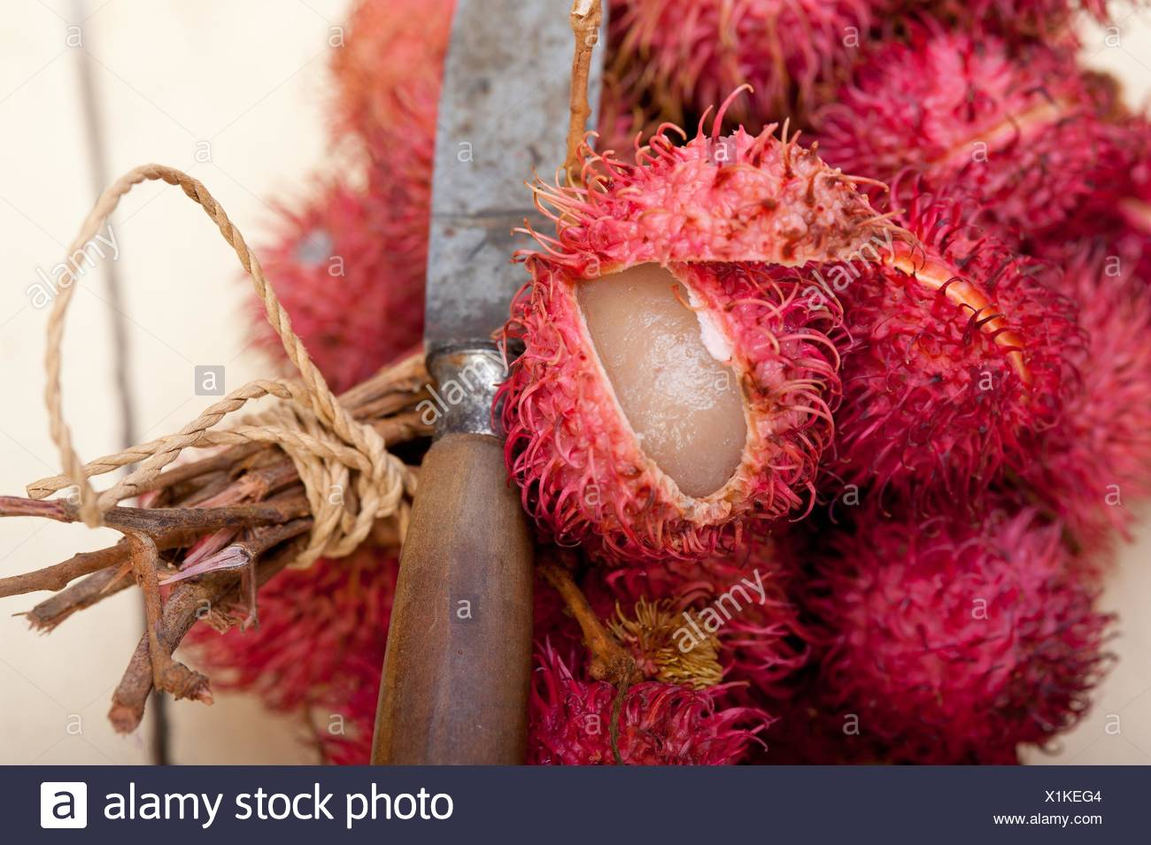 fresh tropical rambutan fruits over rustic wood table. Stock Photo