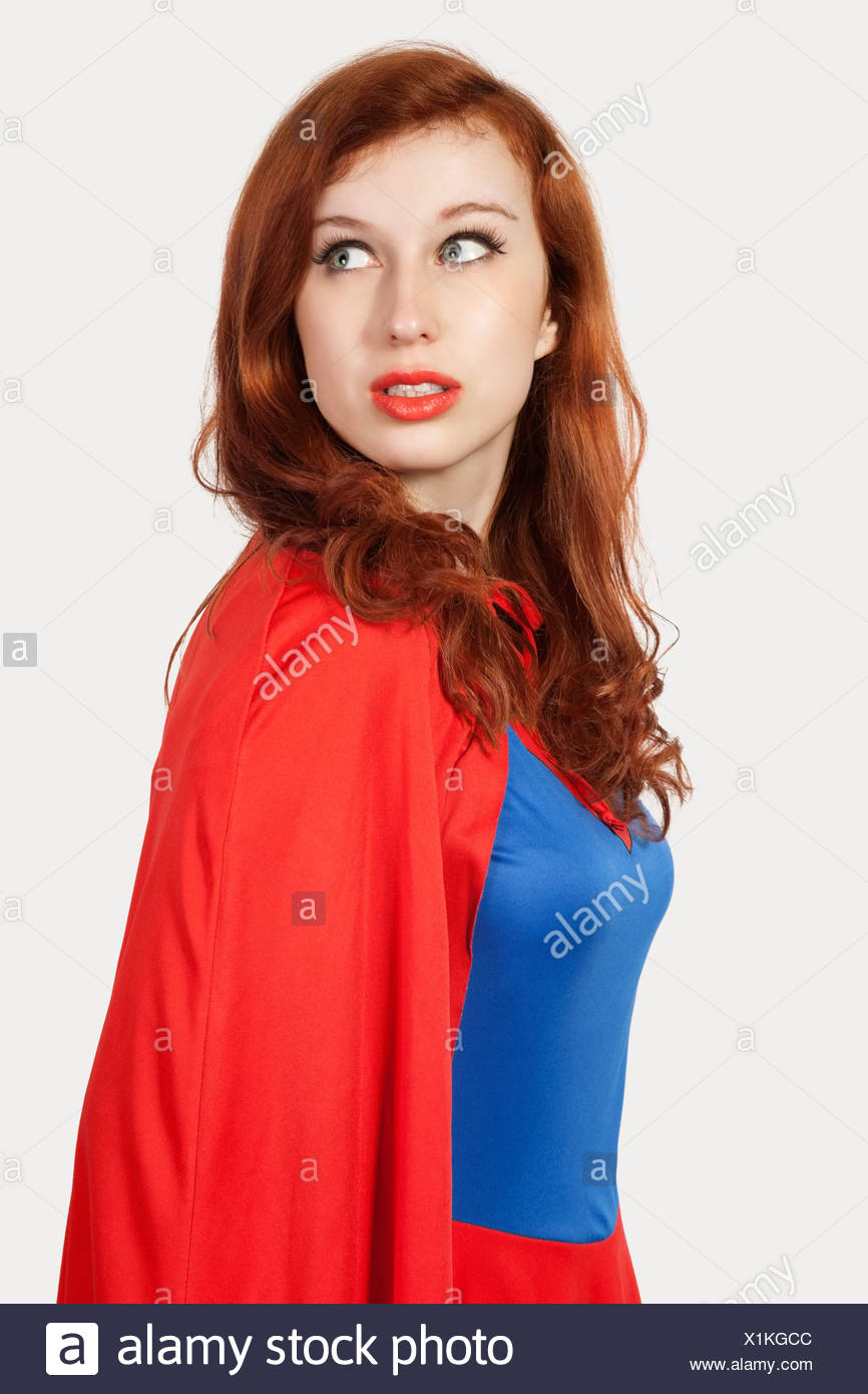 Young woman in superhero costume looking away - Stock Image