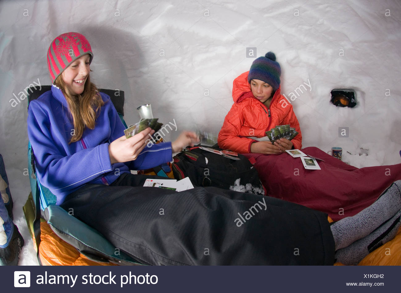 Boy and girl playing cards in snow cave, Silverton, Colorado. - Stock Image