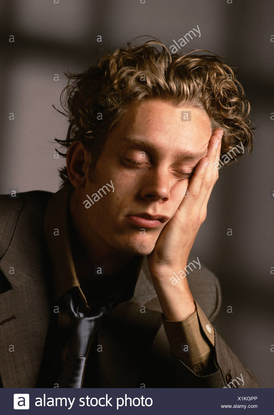 Man sleeping, head resting on hand - Stock Image