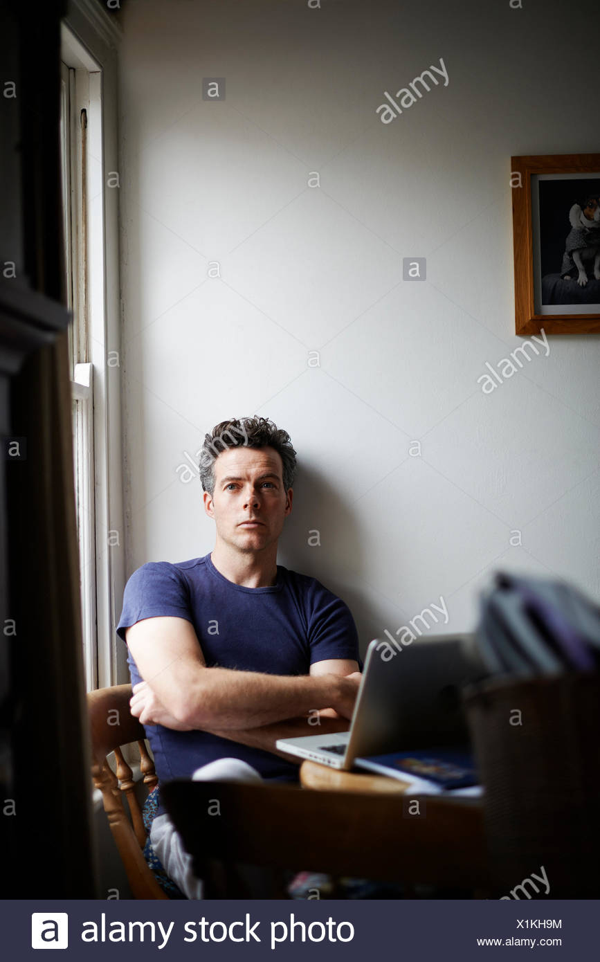 Man sitting at table with open laptop looking away - Stock Image