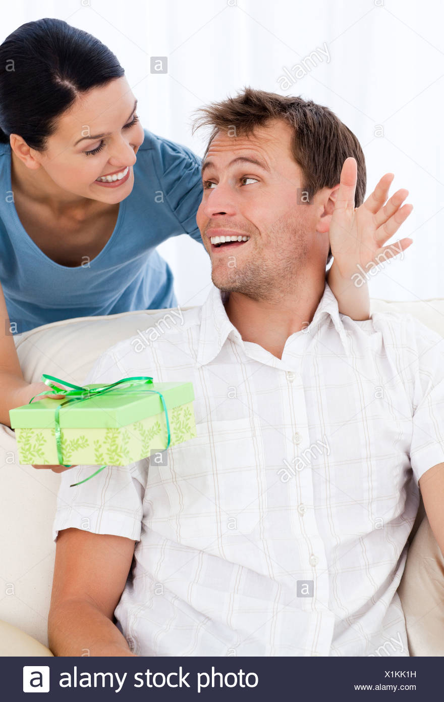 Amazed man receiving a present from his girlfriend - Stock Image