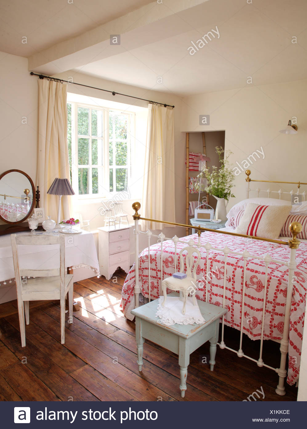 Small blue table below antique brass bed with pink+white ...