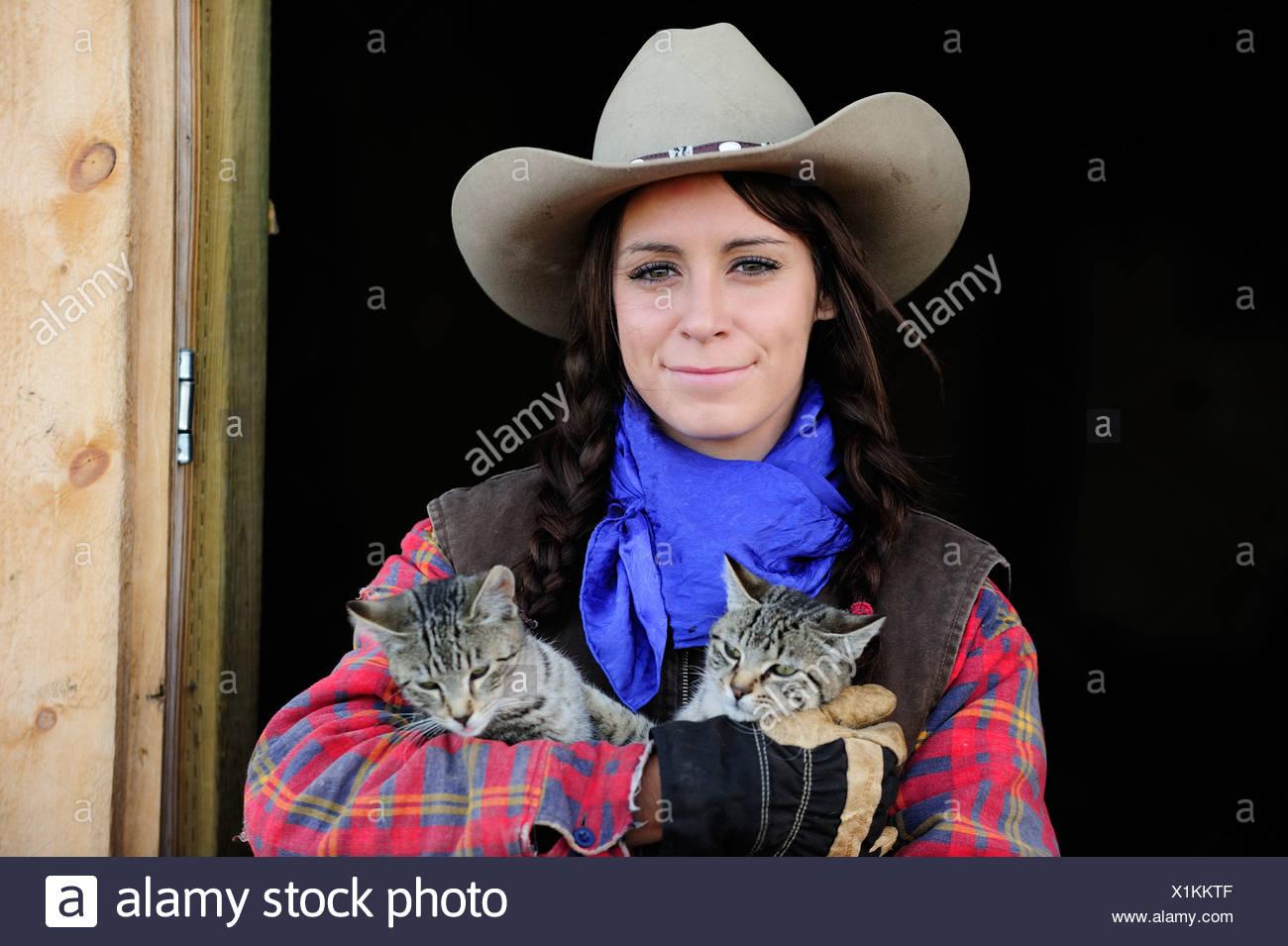 Cowgirl with two cats, portrait, Saskatchewan, Canada, North ...