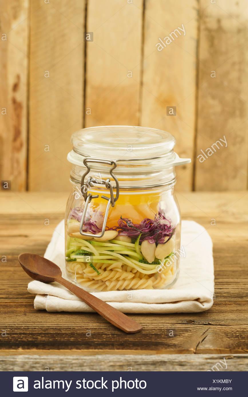 Veganer und vegetarischer Salat zum Mitnehmen im Glas mit Nudeln, spiralisierten Zucchini, Mandeln, Rotkohl und Vinaigrette auf Holz - Stock Image