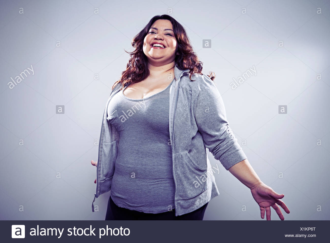 Mid adult woman wearing grey tracksuit top, arms out - Stock Image