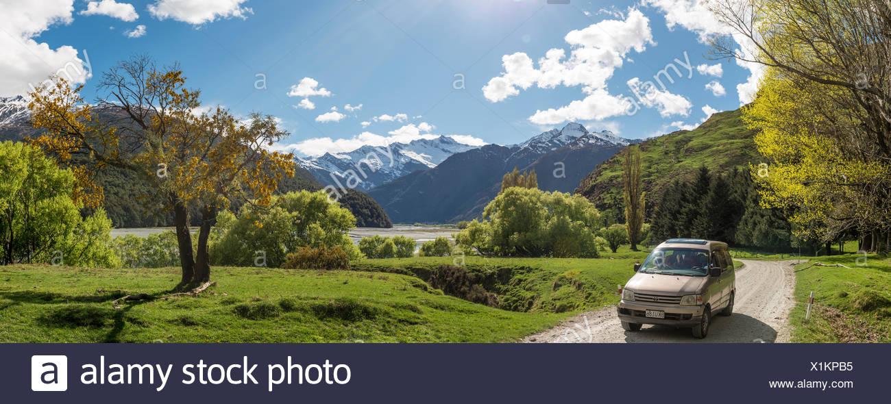 Car on road, Matukituki Valley, snowy Mount Aspiring, Mount Aspiring National Park, Otago, Southland, New Zealand - Stock Image
