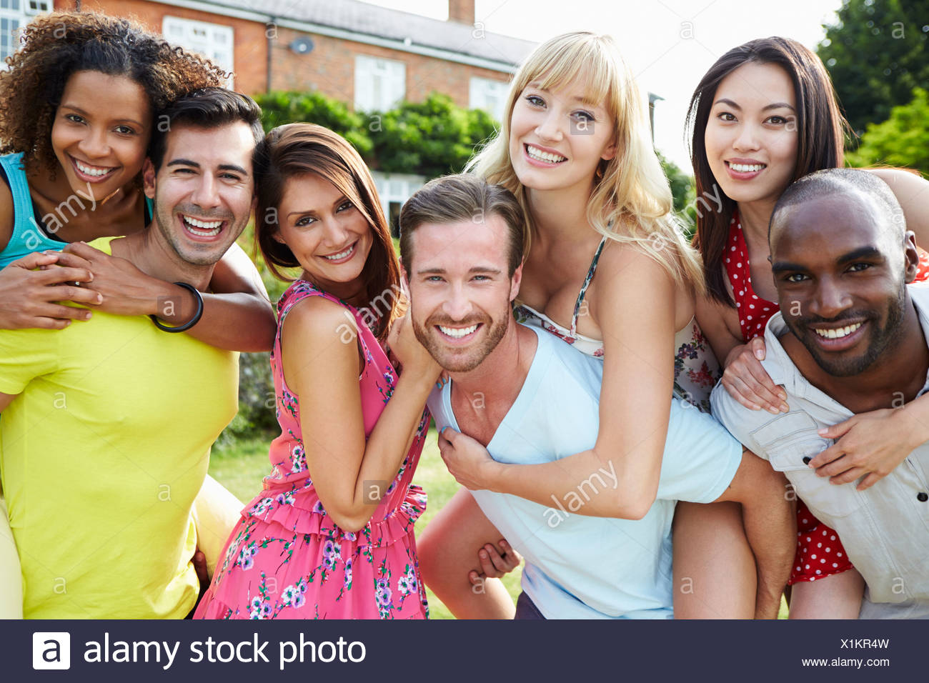 Portrait Of Friends Relaxing In Summer Garden Together Stock Photo