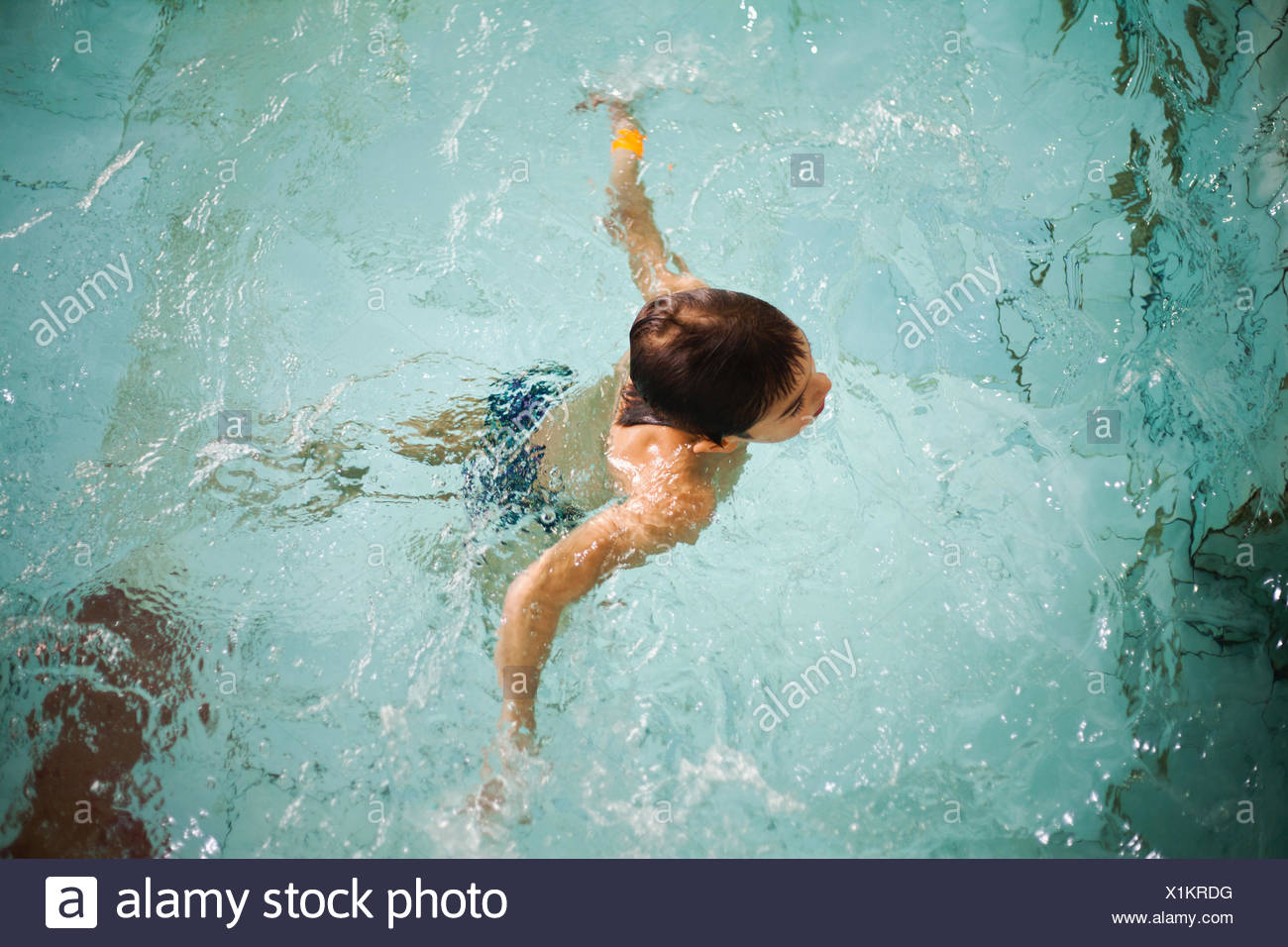 High angle view of boy treating water in swimming pool - Stock Image