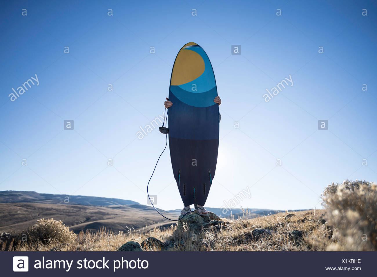 Man holding a surfboard in the desert, Wyoming, America, USA Stock Photo