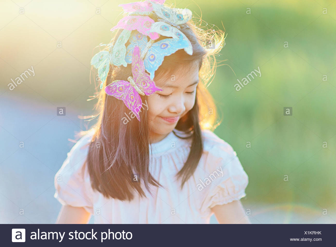 Girl (8-9) with butterflies in hair - Stock Image