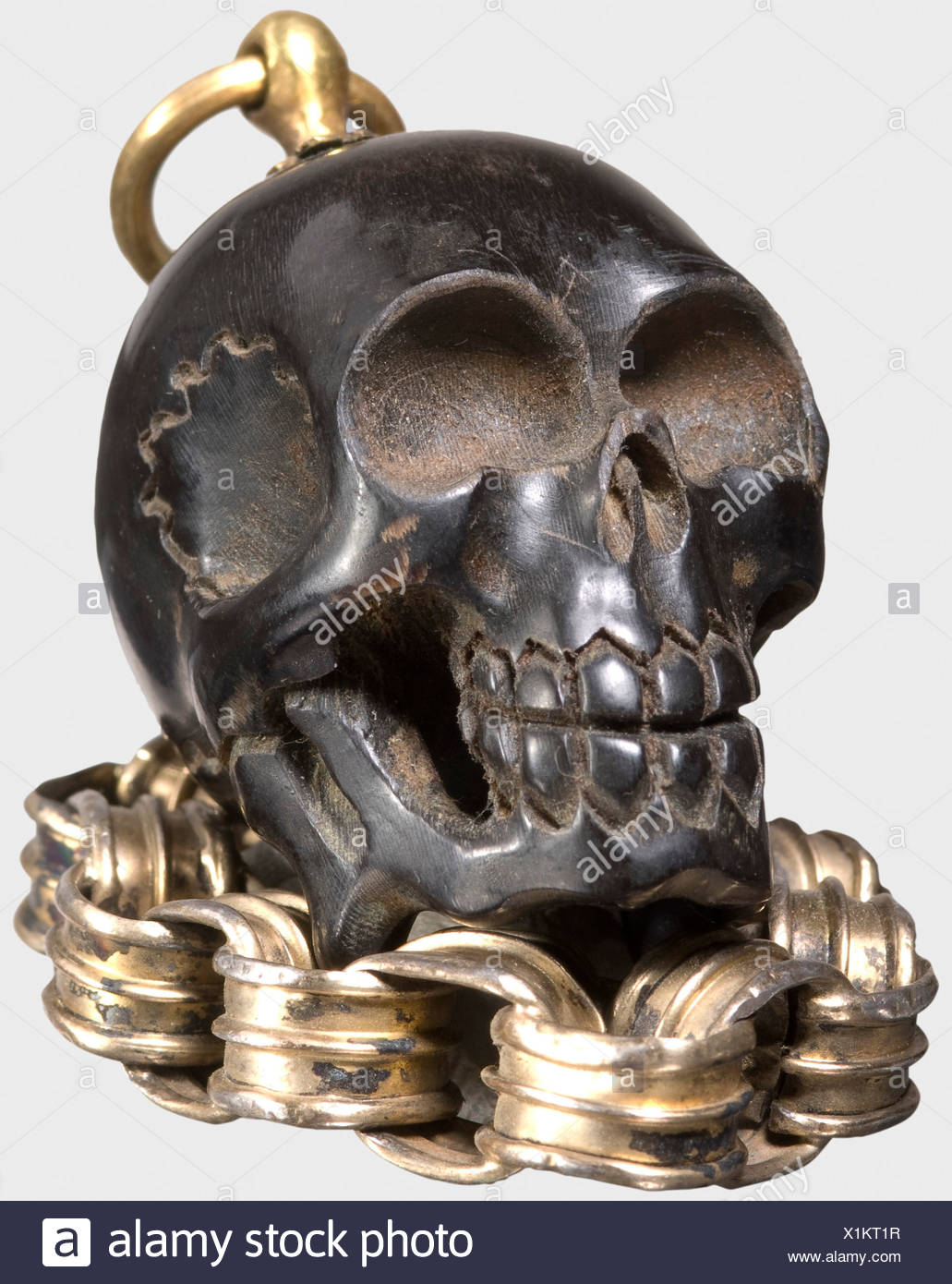 A German miniature memento-mori skull, 17th century A small, delicately carved skull of dark horn. There is a fire-gilded brass suspension ring mounted at the top of the skull, attached to a contoured, gilt silver belcher chain. Height without ring 3.5 cm. Length of the chain 14 cm. historic, historical,, 17th century, handicrafts, handcraft, craft, object, objects, stills, clipping, clippings, cut out, cut-out, cut-outs, jewellery, jewelry, noble, precious, Stock Photo