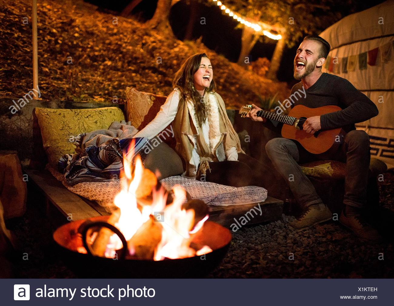 Young couple next to fire and yurt singing and playing guitar - Stock Image