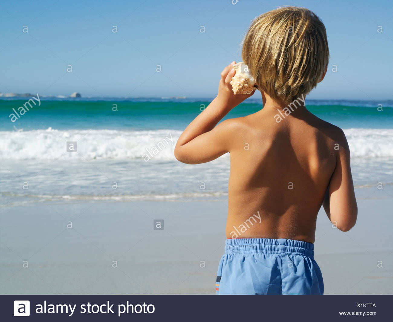 Blonde boy 5 7 standing on beach listening to sea shell looking at horizon over sea rear view Stock Photo