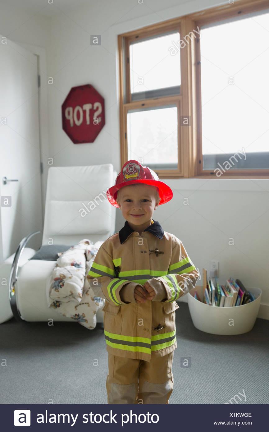 Portrait cute boy in fireman costume - Stock Image