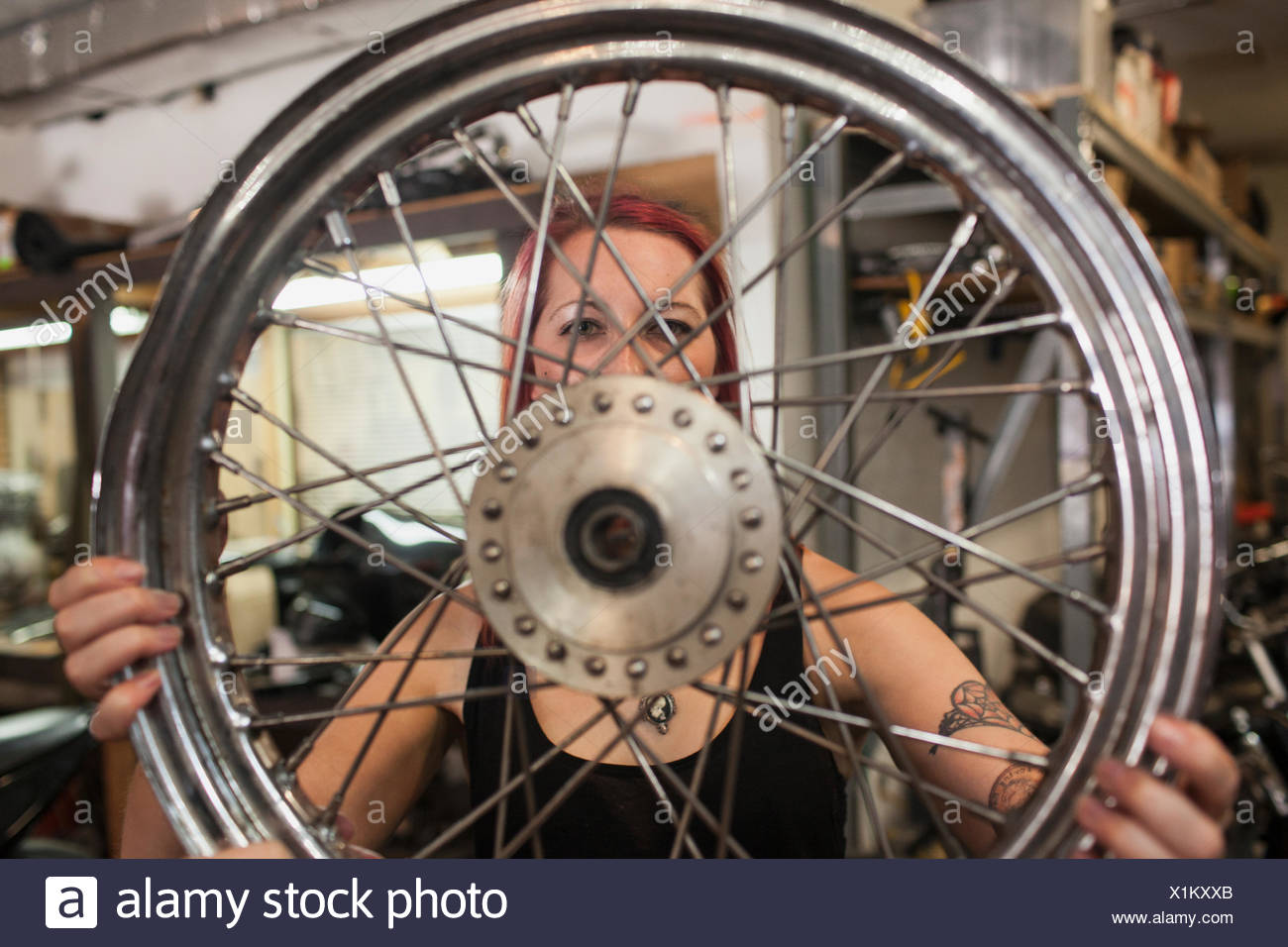 A young woman holding a wheel. - Stock Image