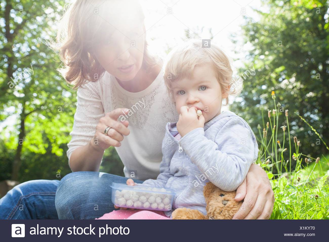 Mother and female toddler eating sweets in park - Stock Image