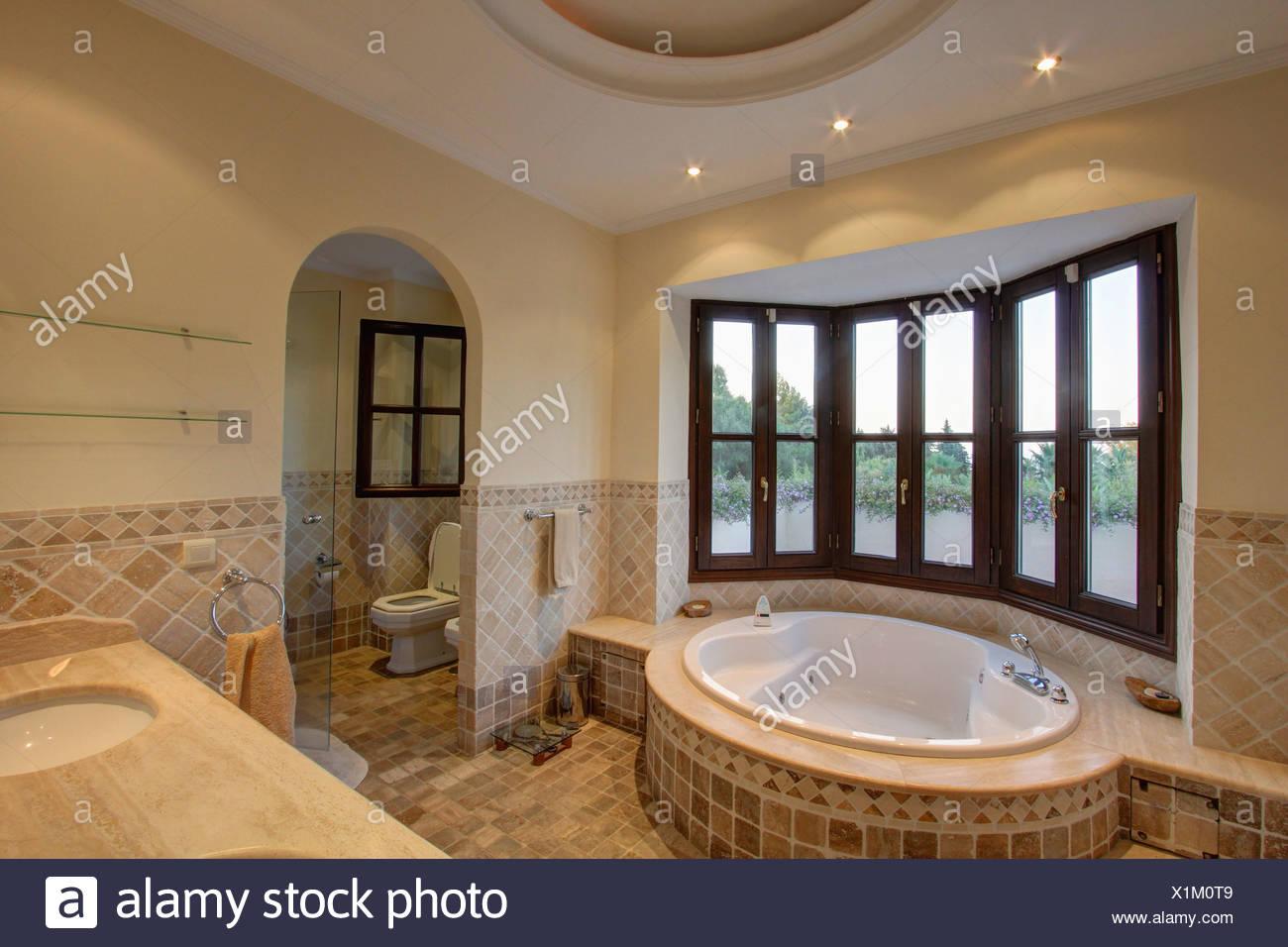 . Oval spa bathtub below bay window in modern Spanish bathroom with