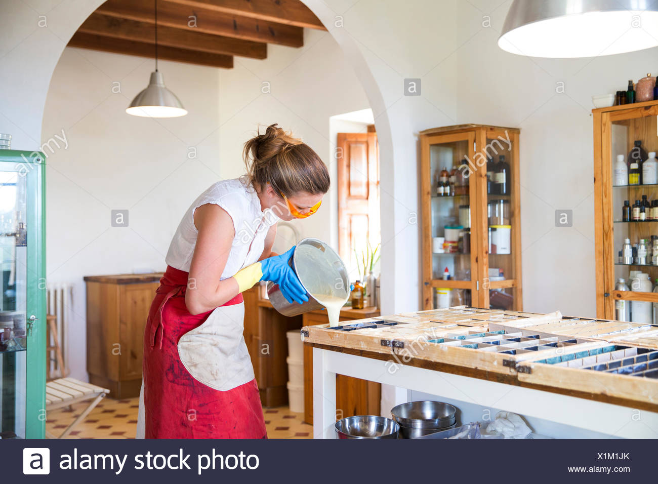 Young woman pouring liquid lavender soap into moulds in handmade soap workshop - Stock Image