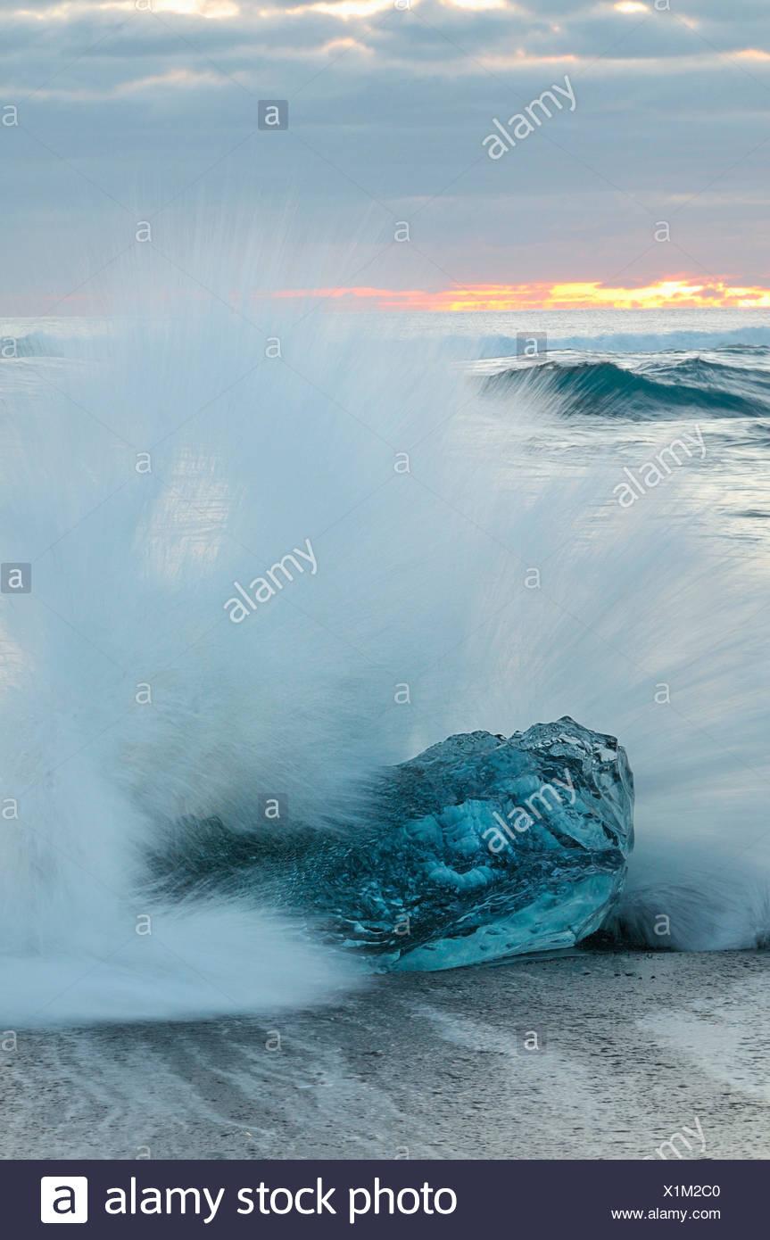 wave that breaks on ice on the beach of Jökulsárlón , Iceland - Stock Image