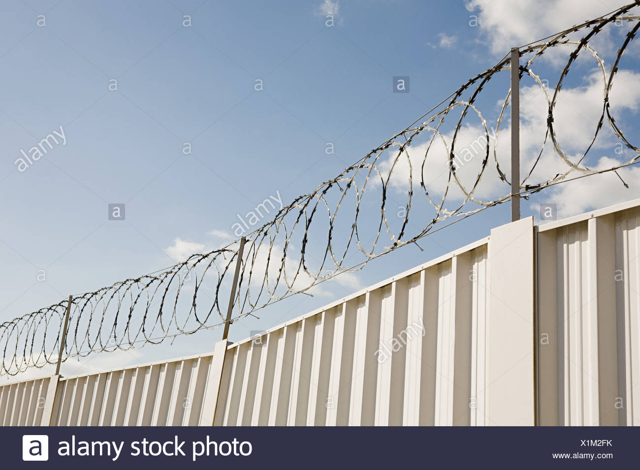 Barbed wire and a fence - Stock Image