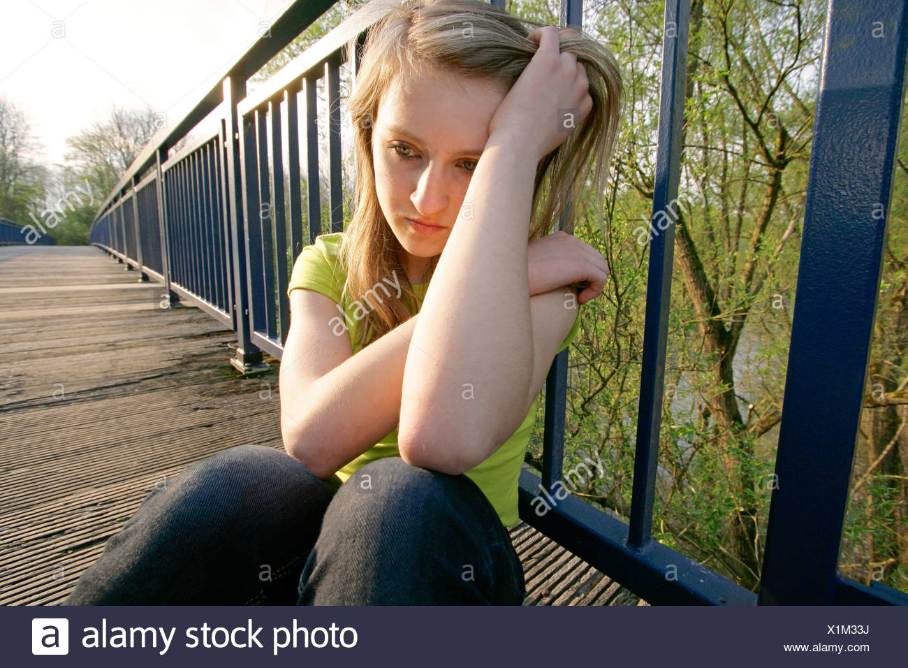 teenage girl sitting on bridge, lost in thought, Germany, Ruhr Area, Herdecke Stock Photo