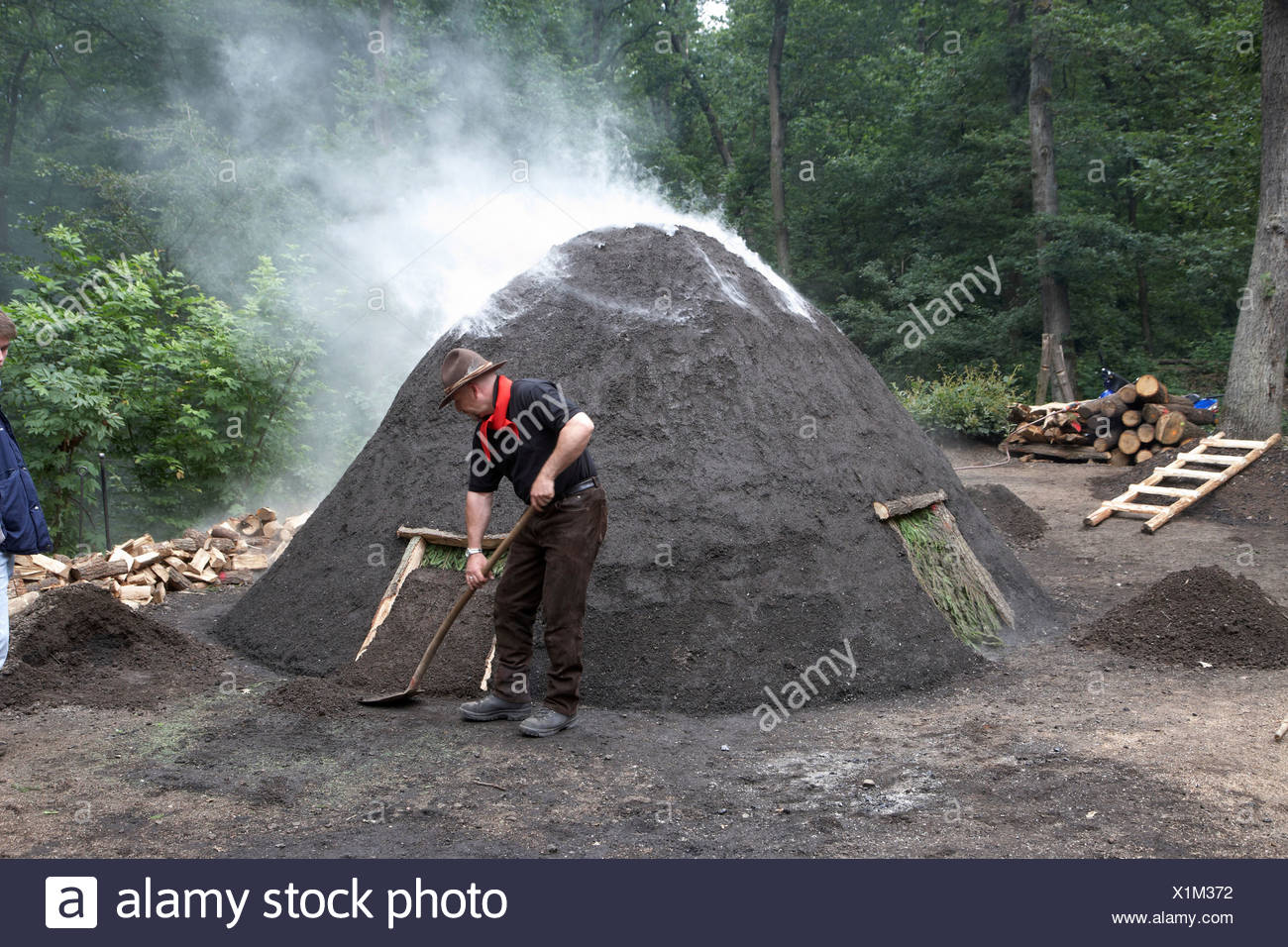 Charburner working on a charcoal kiln, demonstration during the Koehlertage or charcoal burner days Boppard for the conservation - Stock Image