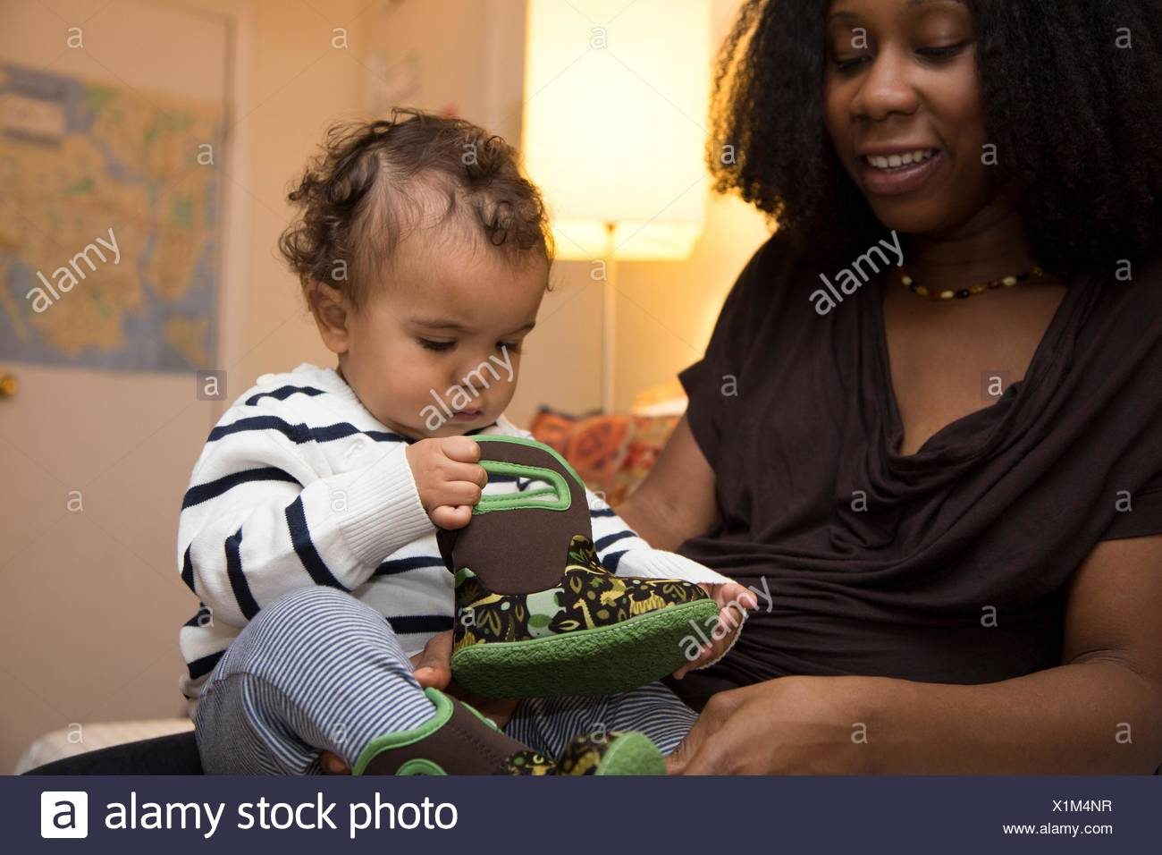 Mid adult woman and curious toddler daughter with baby boot - Stock Image