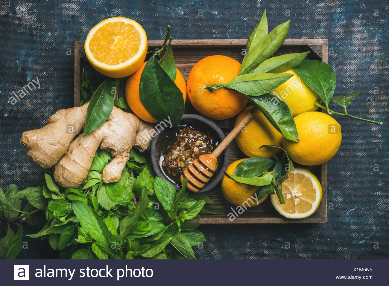 Ingredients for making immunity boosting natural drink. Lemons, oranges, mint, ginger, honey in wooden box over plywood background, top view. Clean ea - Stock Image