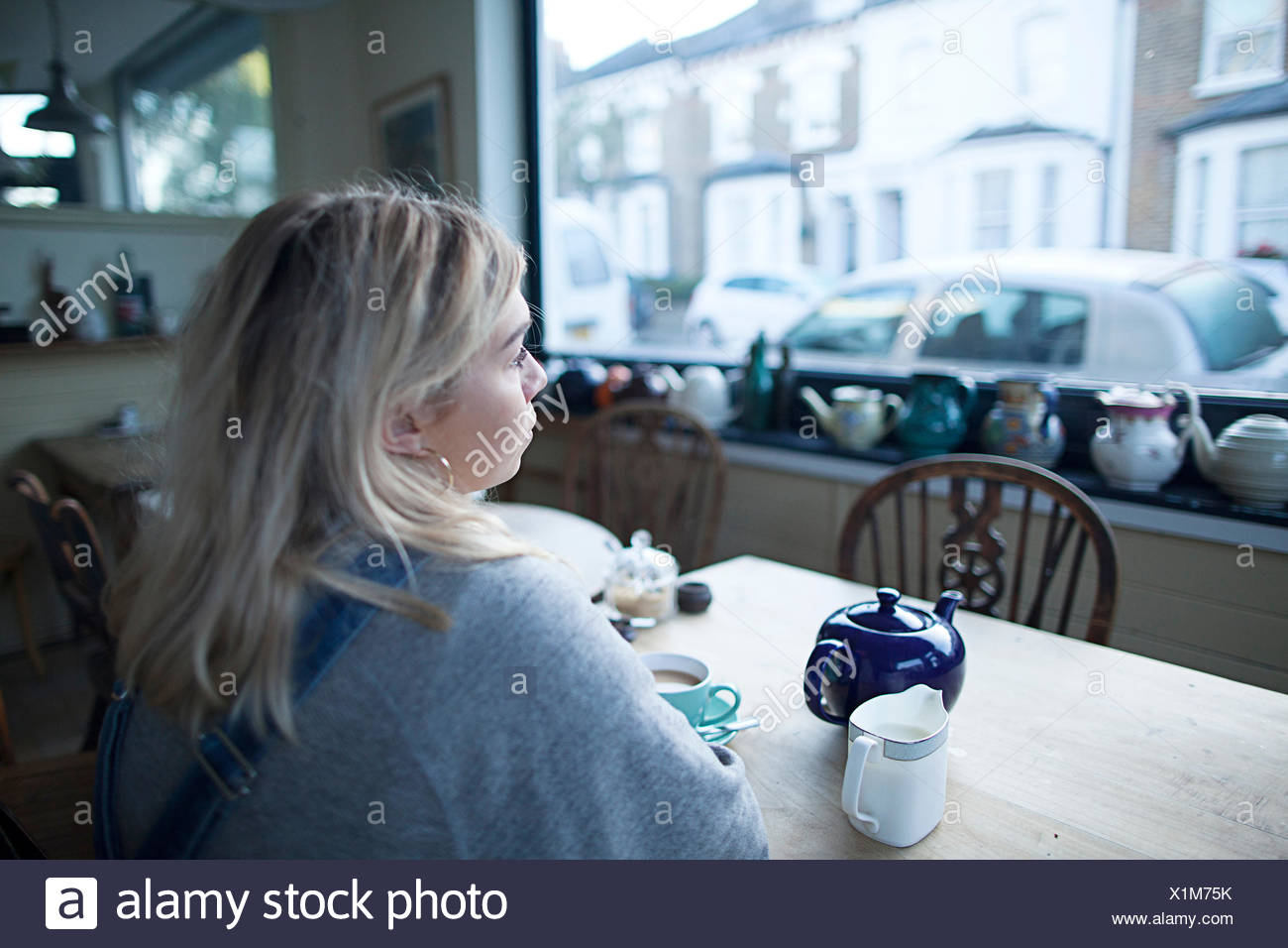 Young woman sitting in cafe, cup of tea and teapot on table, looking out of window - Stock Image