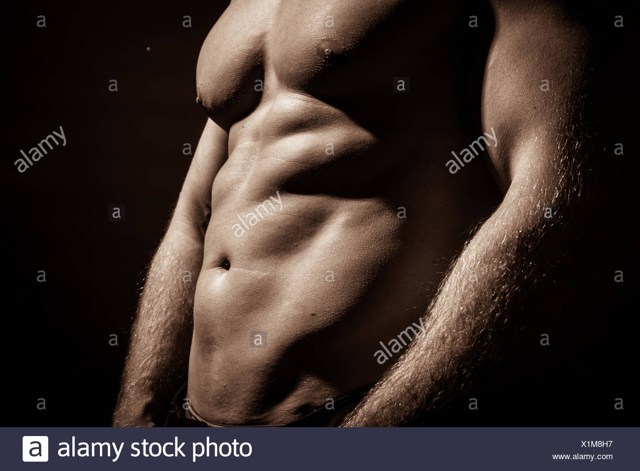 Midsection Of Shirtless Muscular Man Standing Against Black Background - Stock Image