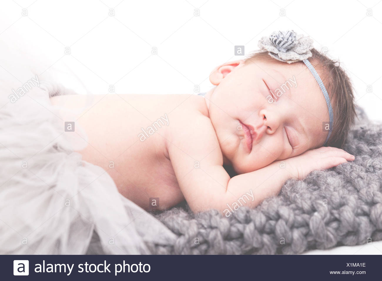 Portrait of a newborn baby girl sleeping on blanket - Stock Image