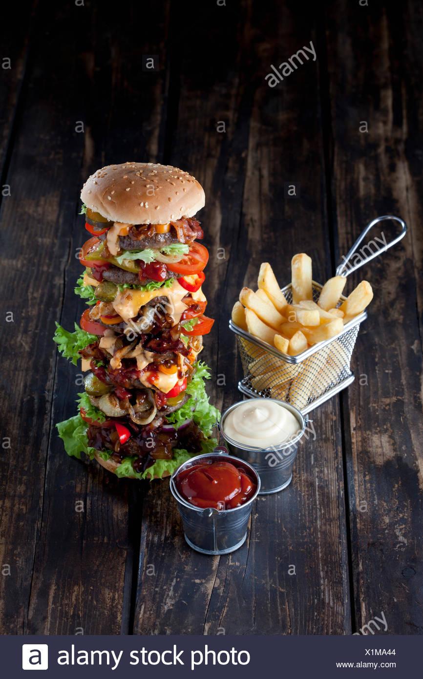 Extra large hamburger with fries, mayonnaise and ketchup - Stock Image