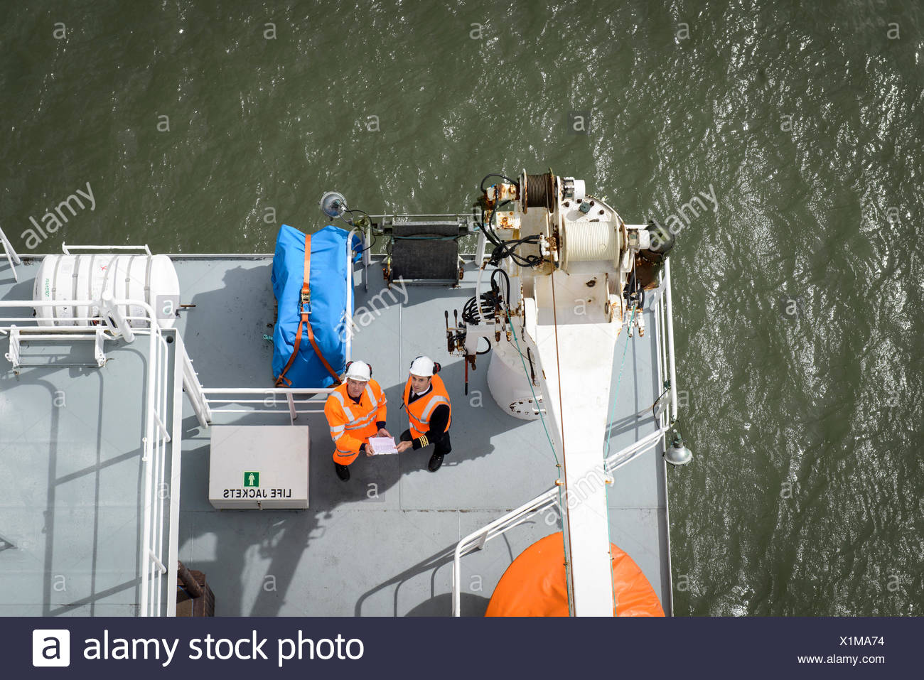 Ship's captain and worker on deck of container ship, overhead view - Stock Image