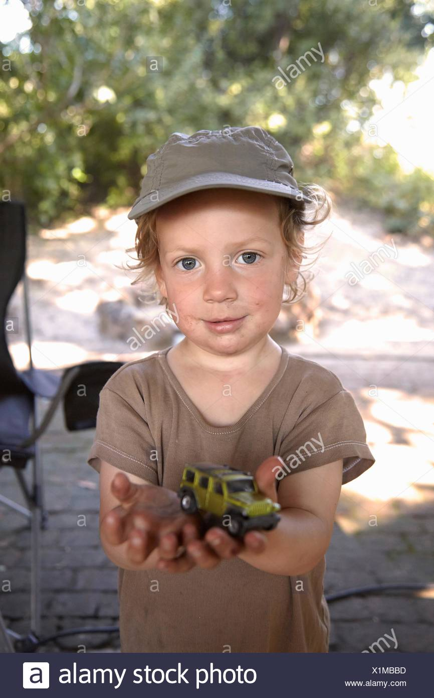 Portrait of young boy holding toy car - Stock Image