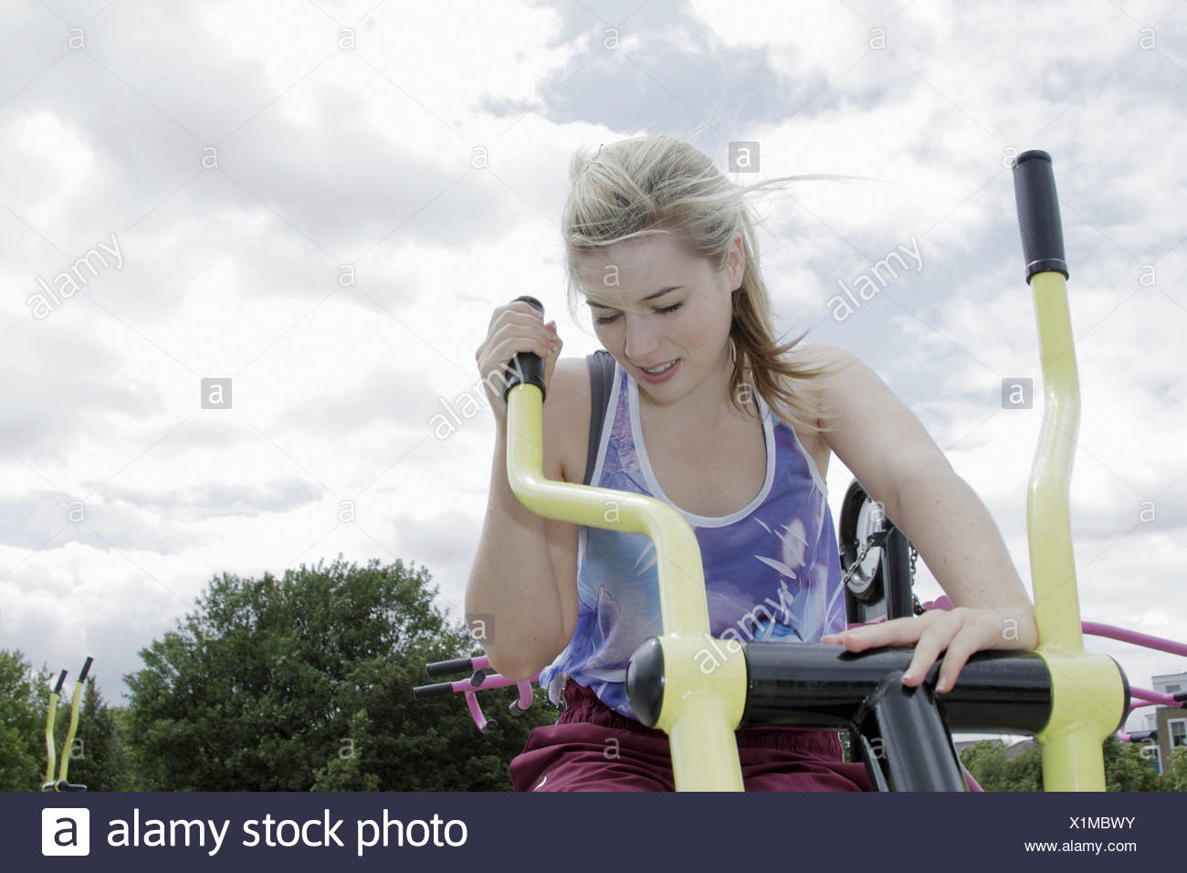 Woman using exercise machine outdoors - Stock Image
